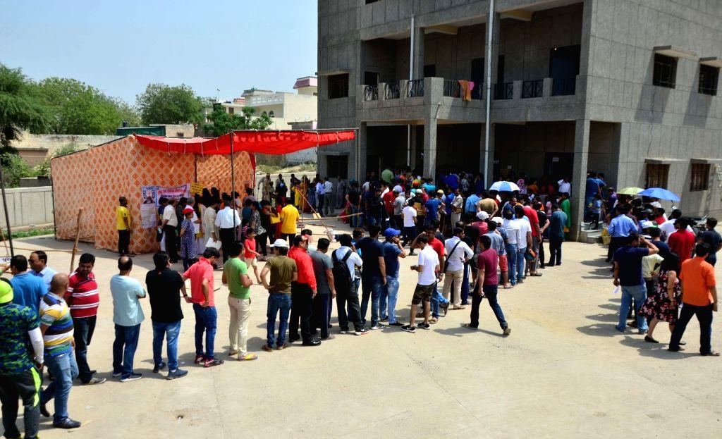 Gautam Buddh Nagar: People wait outside a polling booth to caste their vote for the 2019 Lok Sabha elections, in Uttar Pradesh's Gautam Buddh Nagar, on April 11, 2019.