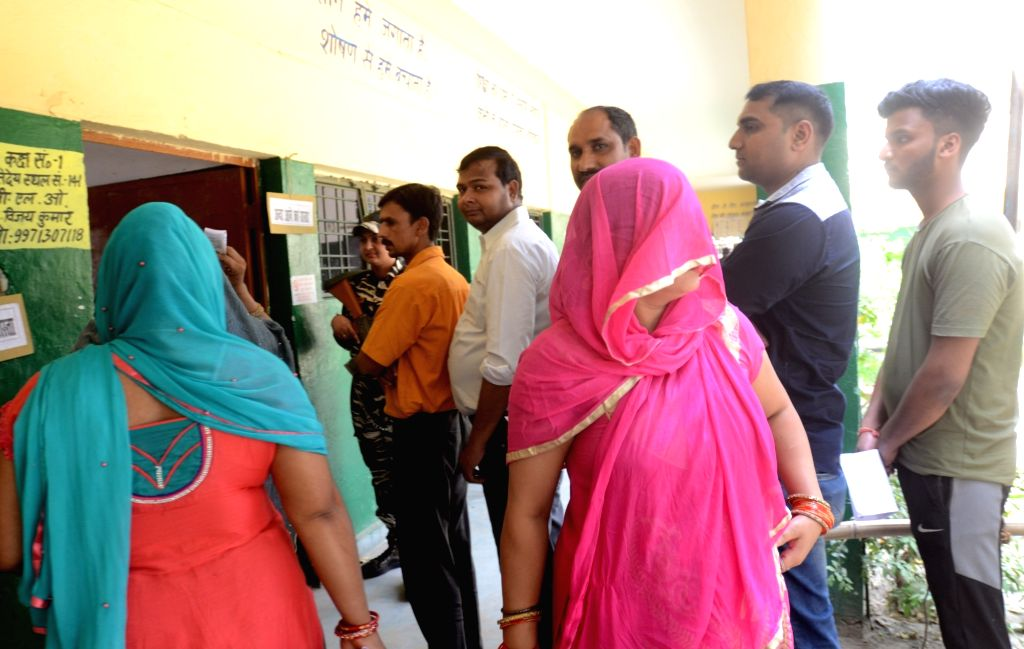 Gautam Buddh Nagar: People wait outside a polling booth to caste their vote for the 2019 Lok Sabha elections, at a polling booth in Uttar Pradesh's Gautam Buddh Nagar, on April 11, 2019.