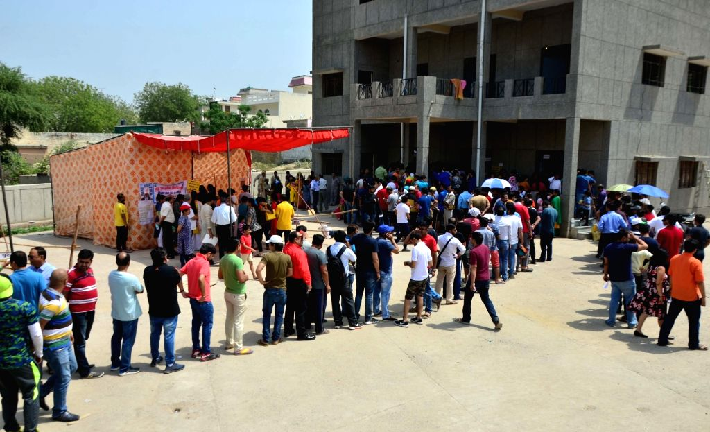 Gautam Buddh Nagar: People wait outside a polling booth to caste their vote for the 2019 Lok Sabha elections, in Uttar Pradesh's Gautam Buddh Nagar, on April 11, 2019. (Photo: IANS)