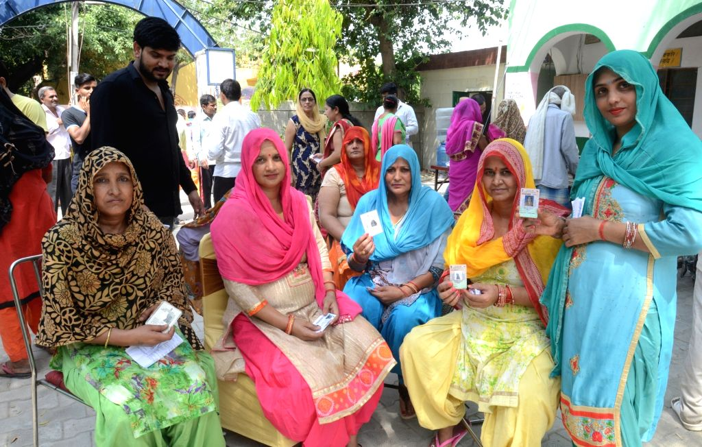 Gautam Buddh Nagar: Women show their voter IDs as they arrive to cast their votes for the first phase of 2019 Lok Sabha elections, at a polling booth in Uttar Pradesh's Gautam Buddh Nagar, on April ...