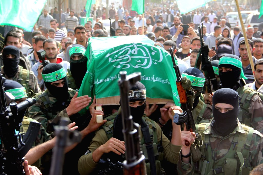 Palestinians carry the body of one of three Hamas militants who were killed in an explosion, during their funeral in the Al-Nusairat refugee camp, in central Gaza ...