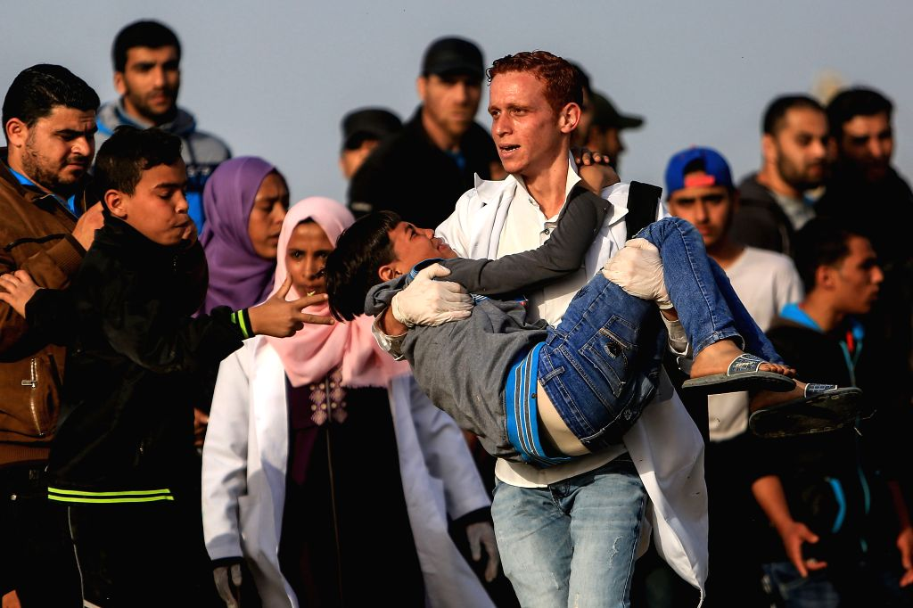 GAZA, April 26, 2019 - A Palestinian medic carries a wounded young man during clashes with Israeli troops on the Gaza-Israel border, east of Gaza City, April 26, 2019. At least 60 Palestinian ...