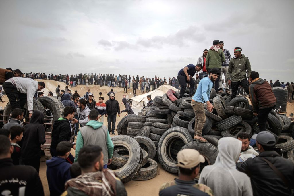 GAZA, April 4, 2018 - Palestinian protestors pile up tyres for burning them during a clash with Israeli soldiers along the Gaza Strip-Israel border, east of the south Gaza Strip city of Khan Yunis, ...