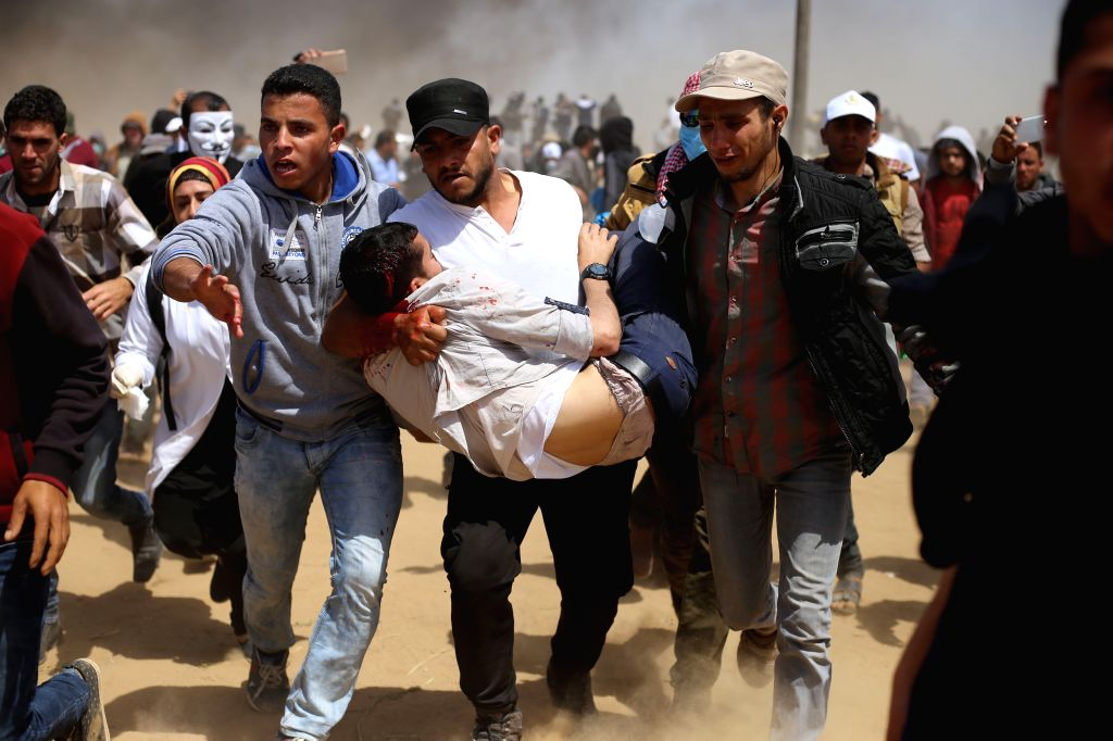 GAZA, April 6, 2018 - Palestinian protesters carry an injured man during clashes on the Gaza-Israel border, east of Gaza City on April 6, 2018. Hundreds of Palestinian demonstrators began Friday to ...