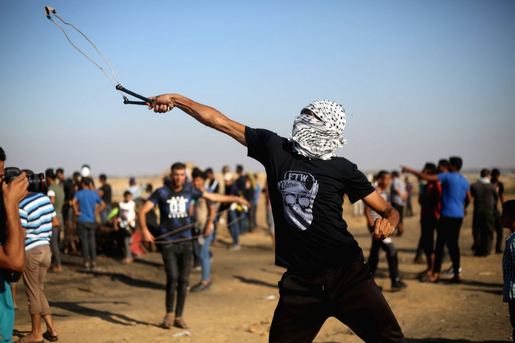 GAZA, Aug. 2, 2019 - A Palestinian protester uses a slingshot to hurl stones at Israeli troops during clashes on the Gaza-Israel border, east of southern Gaza Strip city of Khan Younis, Aug. 2, 2019. ...