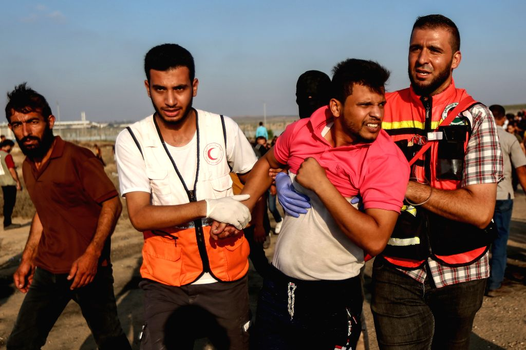 GAZA, Aug. 2, 2019 - Palestinian medics help a wounded man during clashes with Israeli troops on the Gaza-Israel border, east of Gaza City, Aug. 2, 2019. At least 51 Palestinians were injured on ...