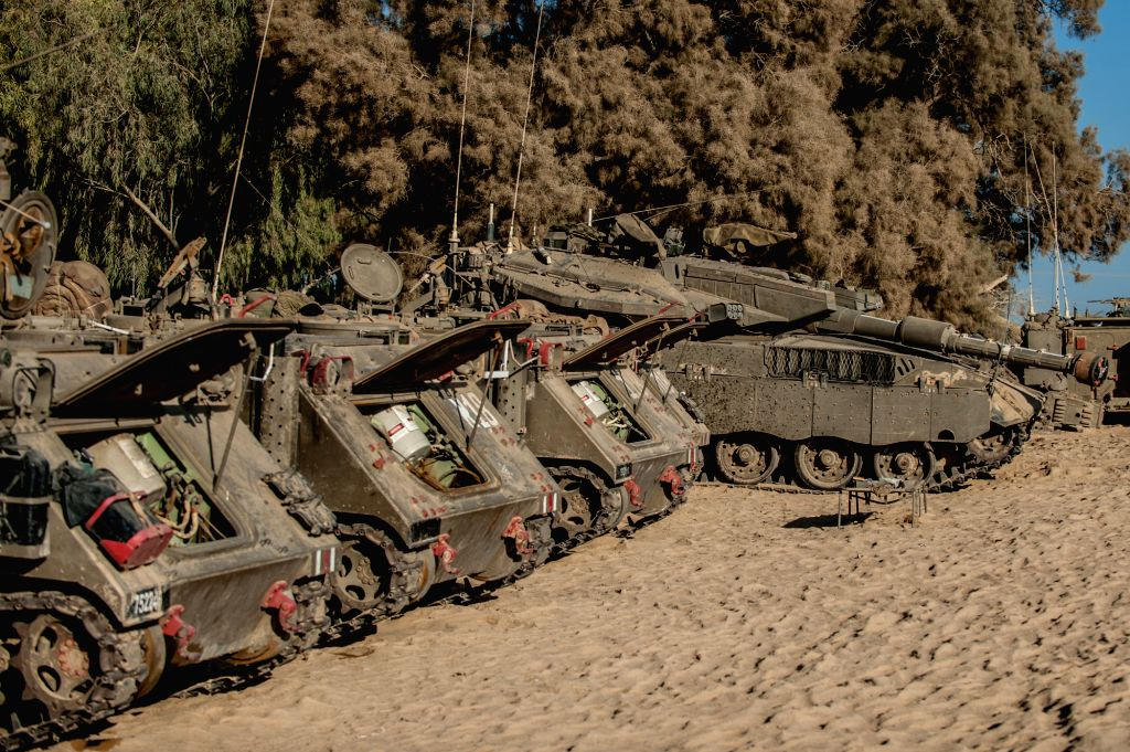 An Israeli Merkava tank and APCs are seen at an army deployment area in southern Israel bordering the Gaza Strip, on Aug. 20, 2014. Israel will step up the ... - Benjamin Netanyahu