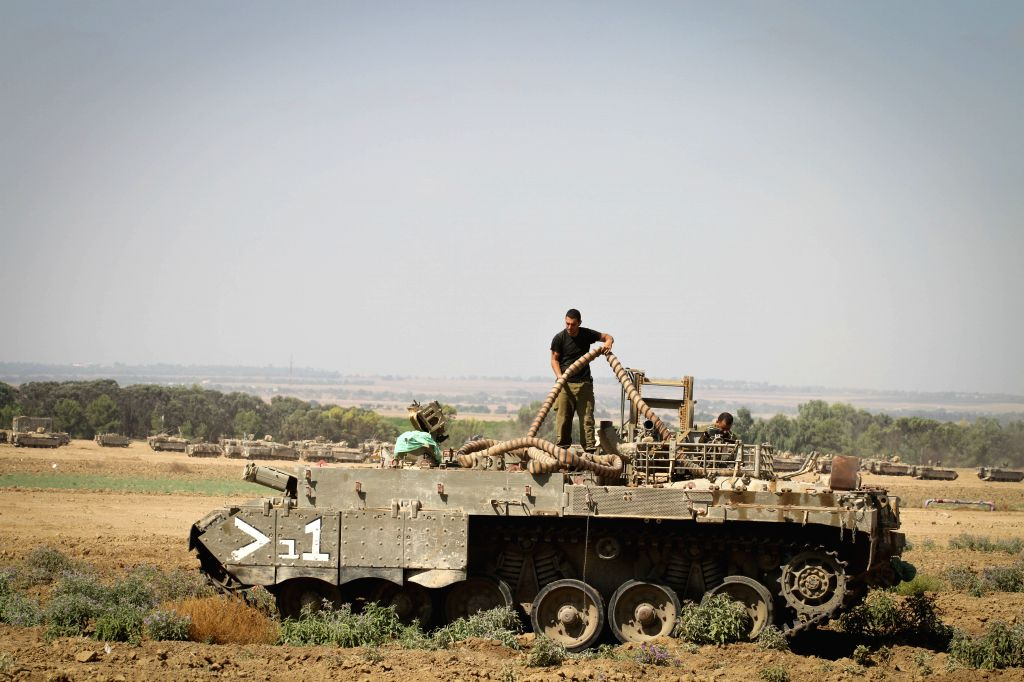 Israeli soldiers carry out maintenance on an APC at an army deployment area in southern Israel bordering the Gaza Strip, on Aug. 21, 2014. Israel approved on ...