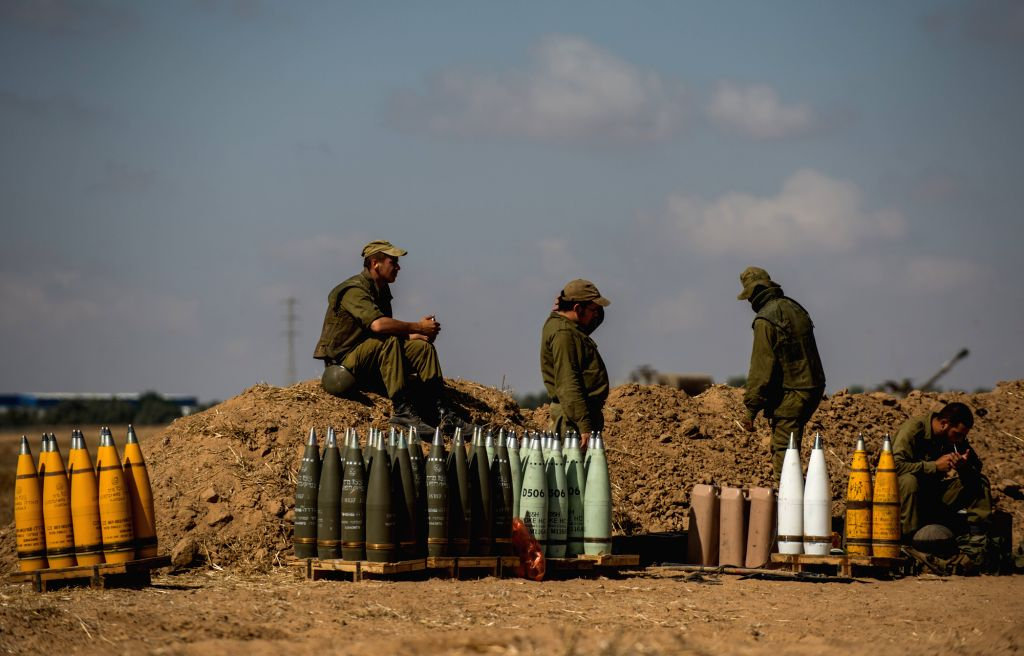 Israeli soldiers rest beside shells for a 155mm M109 Dores self-propelled howitzer at a position in Southern Israel near the border with Gaza, on the seventh ...