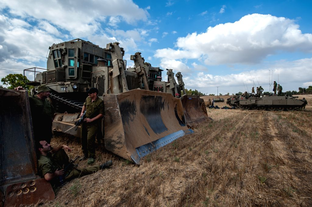 Israeli soldiers gather around armored vehicles in the field in southern Israel near the border with Gaza, on July 18, 2014, the 11th day of Operation ... - Benjamin Netanyahu