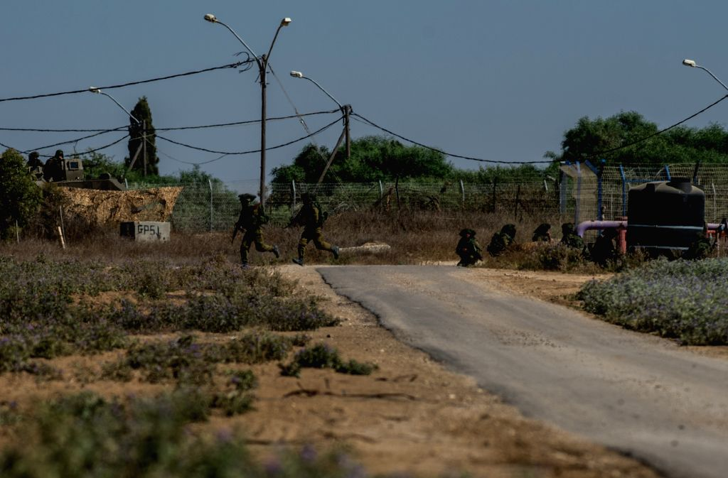 Two Israeli soldiers change their positions during a crossfire with Palestinian militants in the field of southern Israel near the border with Gaza, on the ...