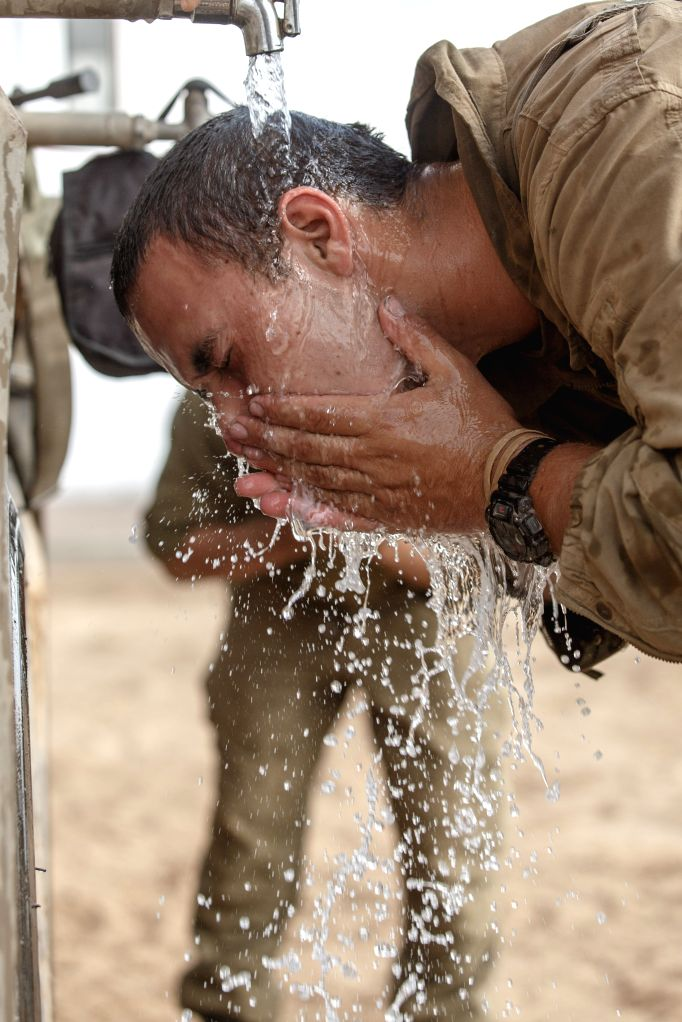 An Israeli soldier washes his face at an army deployment area in southern Israel near the border with Gaza, on the 17th day of Operation Protective Edge, on ...