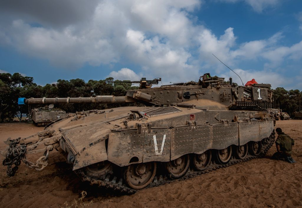 An Israeli soldier checks the caterpillar track of a Merkava tank at an army deployment area in southern Israel near the border with the Gaza Strip, on July 28,