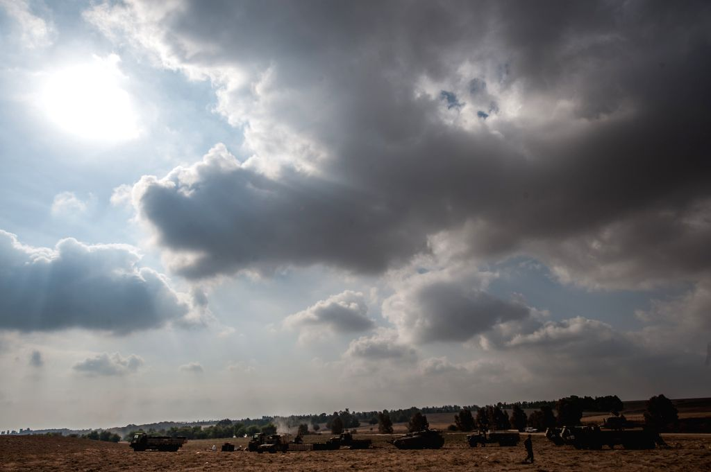 An Israeli soldier walks at an army deployment area in southern Israel near the border with the Gaza Strip, on July 28, 2014. Israel's top political and defense