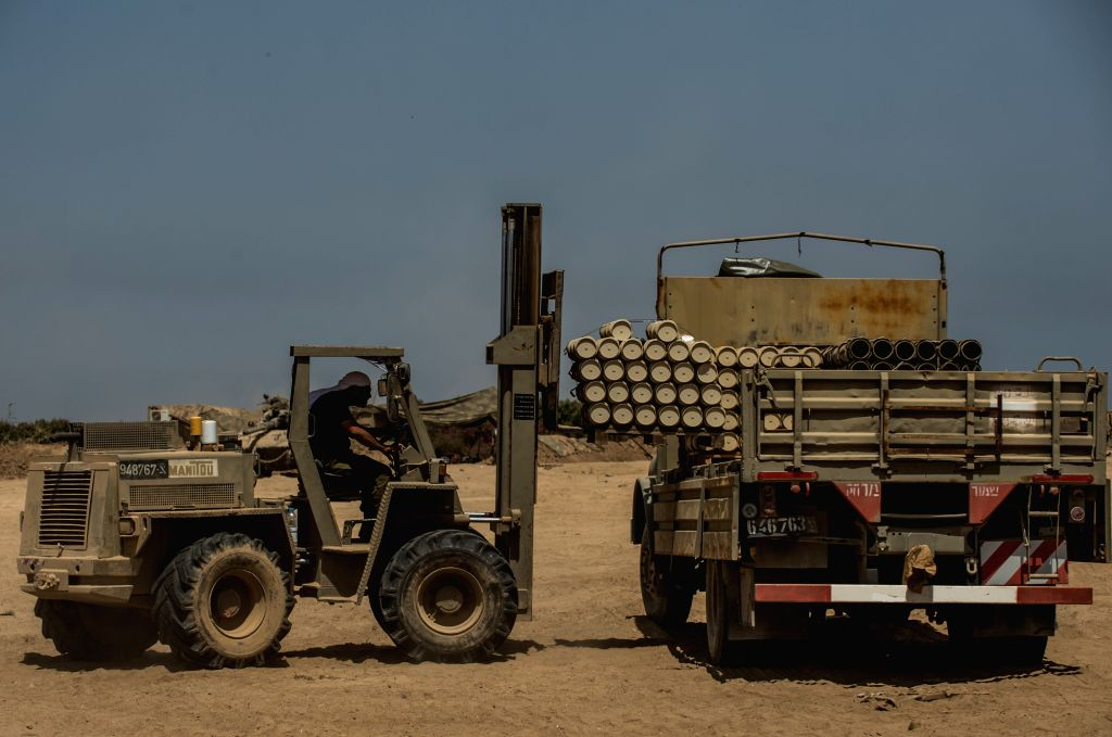 An Israeli forklift loads shells to a truck at an army deployment area in southern Israel near the border with Gaza, on July 30, 2014. Three Israeli soldiers ...