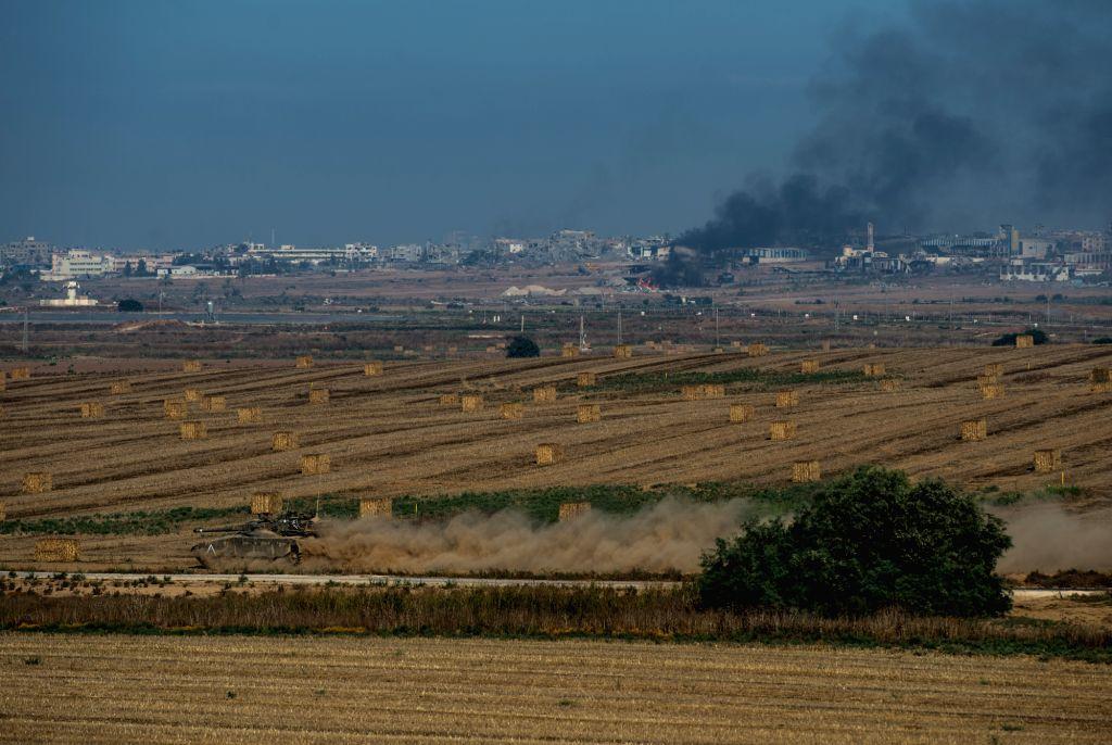 An Israeli Merkava tank runs in the field in southern Israel near the border with Gaza while smoke rises in northern Gaza Strip, on July 30, 2014. Three Israeli