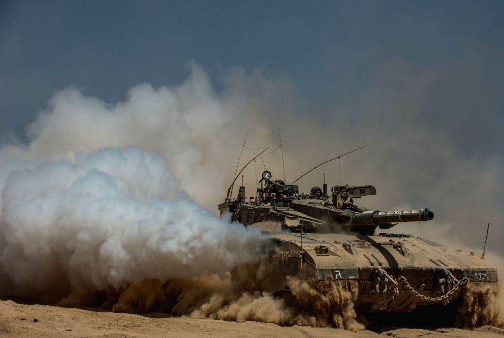 An Israeli Merkava tank runs in the field in southern Israel near the border with Gaza, on July 30, 2014. Three Israeli soldiers were killed in the Gaza Strip ..