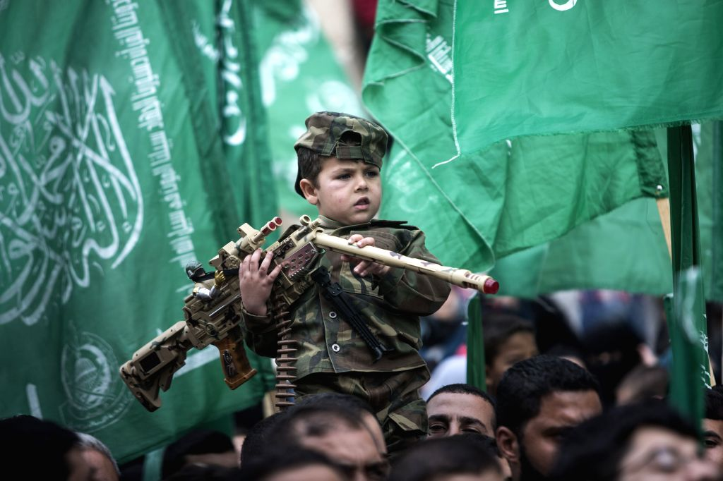 A Palestinian boy wears the headband of Hamas armed wing as he sits on the shoulder of his father during a rally ahead of the 27th  founding anniversary of Hamas, in ..