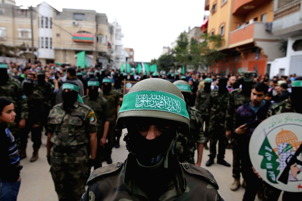 A Palestinian militant wears the headband of Hamas armed wing during a rally ahead of the 27th  founding anniversary of Hamas, in the southern Gaza Strip city of ...
