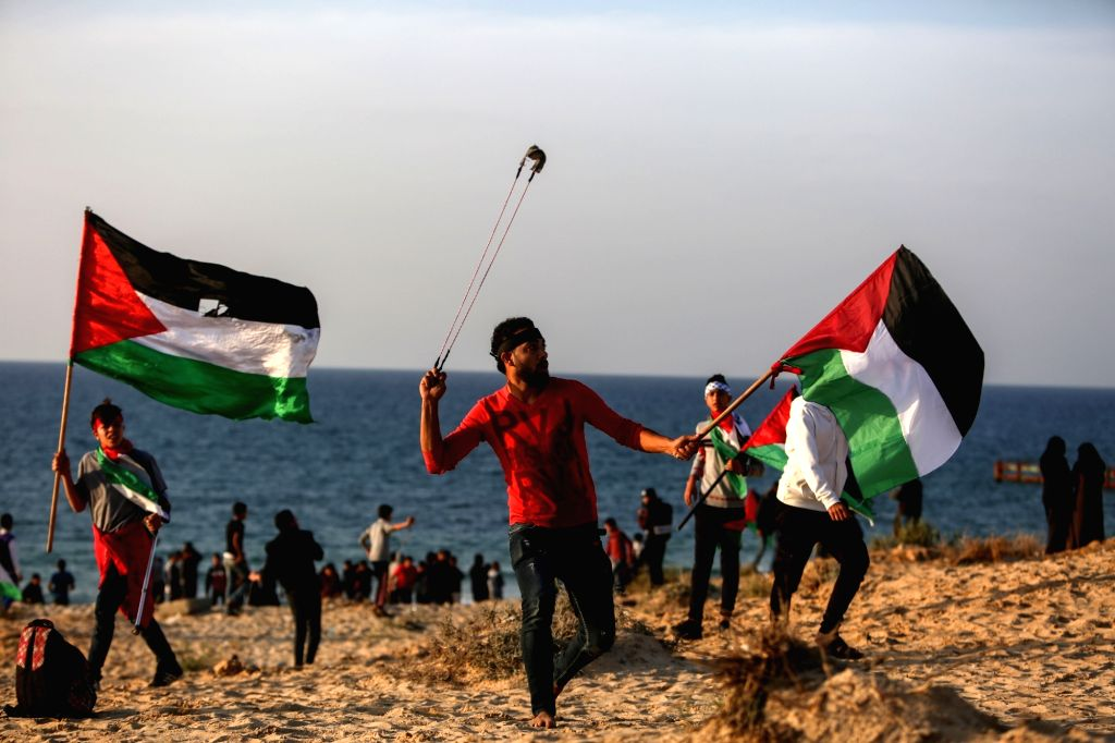 GAZA, Dec. 3, 2018 - A Palestinian protester uses a slingshot to hurl stones at Israeli troops on a beach near the maritime border with Israel, in the northern Gaza Strip, Dec. 3, 2018. Four ...