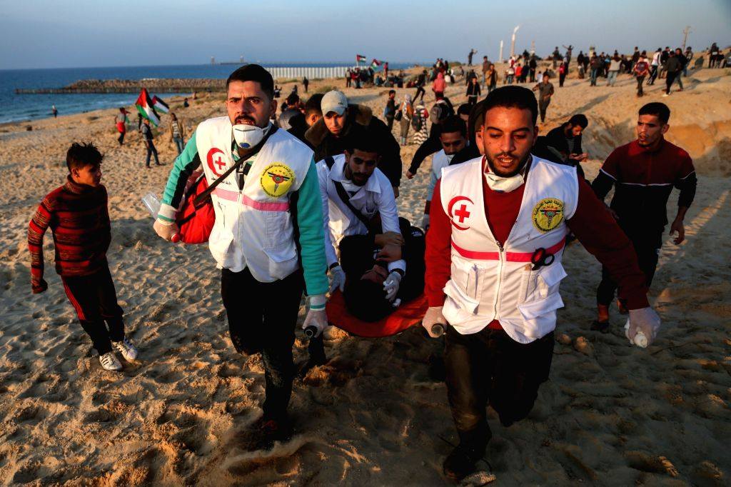 GAZA, Dec. 3, 2018 - Palestinian medics carry a wounded man during clashes with Israeli troops on a beach near the maritime border with Israel, in the northern Gaza Strip, Dec. 3, 2018. Four ...