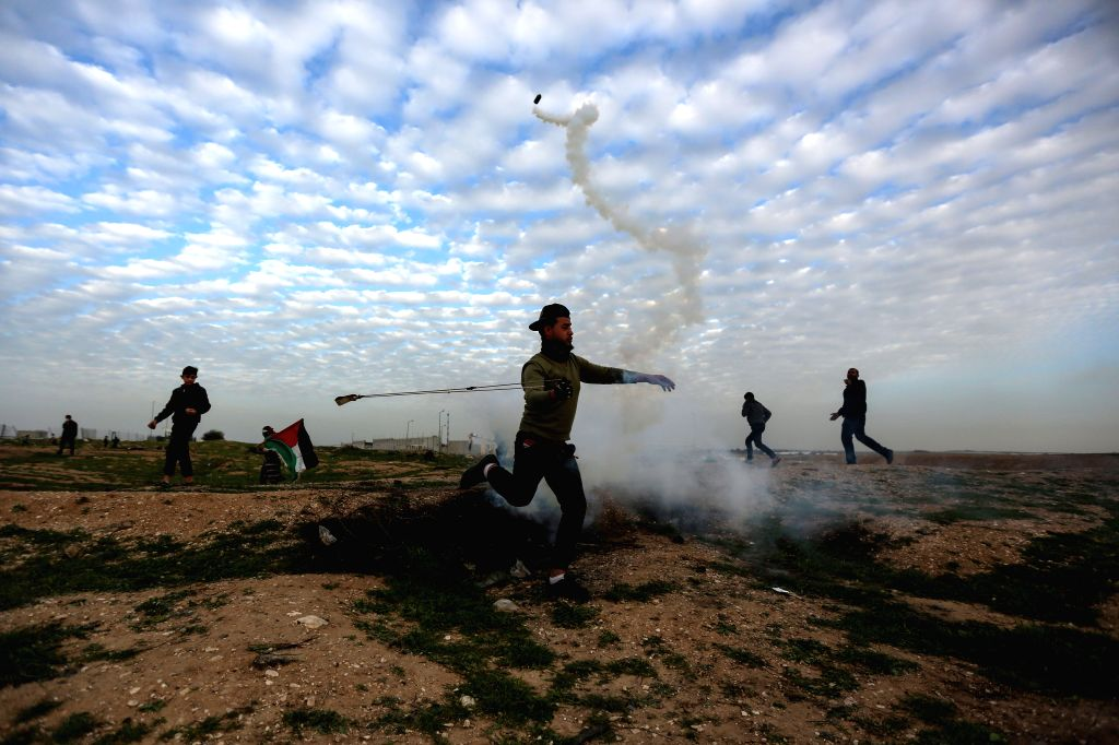 GAZA, Feb. 1, 2019 - A Palestinian protester uses a slingshot to throw back a tear gas canister fired by Israeli troops during clashes on the Gaza-Israel border, east of Gaza City, on Feb. 1, 2019. ...