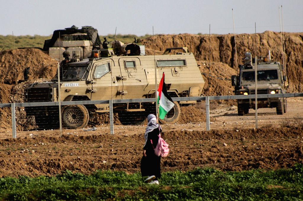 GAZA, Feb. 1, 2019 - A Palestinian woman holds a Palestinian flag during clashes with Israeli troops on the Gaza-Israel border, east of Gaza City, on Feb. 1, 2019. Clashes broke out on Friday ...