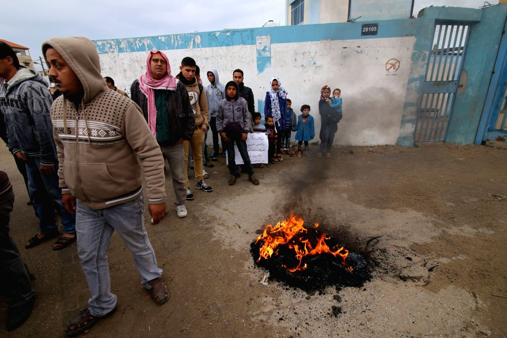 Palestinian stand beside burning tires during a protest calling for reconstruction of their houses which destroyed during a 51-day war between Israel and Hamas ...