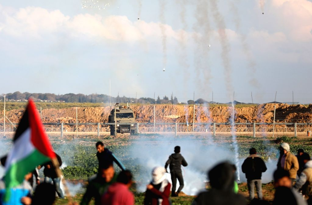 GAZA, Feb. 22, 2019 - Palestinians run to take cover from tear gas canisters fired by Israeli troops on the Gaza-Israel border, east of Gaza City, on Feb. 22, 2019. One Palestinian teenager was ...