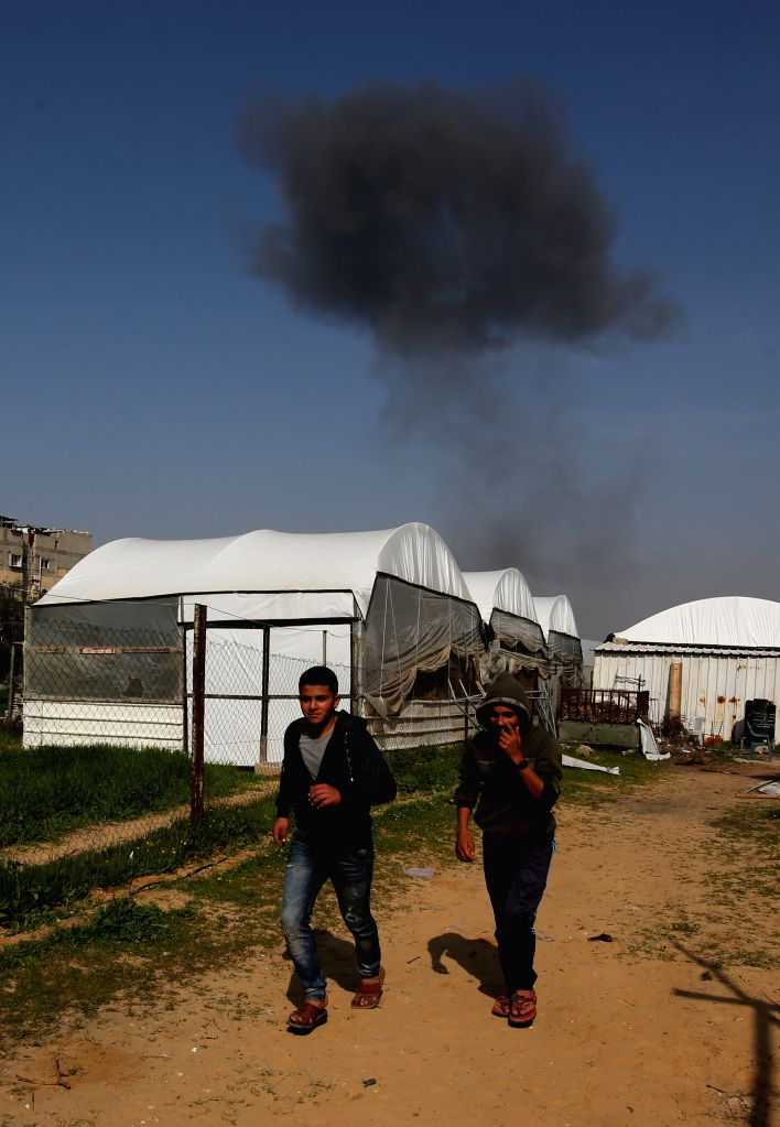 GAZA, Feb. 28, 2017 - Palestinians walk as smoke billows following an Israeli airstrike in the southern Gaza Strip city of Rafah, on February 27, 2017. Israel's military spokesperson said the air ...