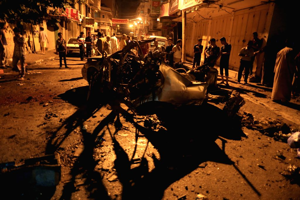Palestinians gather around the remains of the car which police said was targeted in an Israeli airstrike in Gaza City, July 9, 2014. Ambulance teams said that the ...