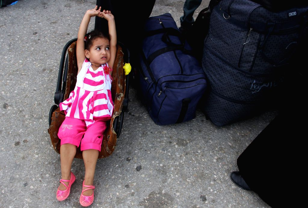Gaza July 12, 2014  - A Palestinian girl hoping to cross into Egypt sits beside her luggage at the Rafah crossing between Egypt and the southern Gaza Strip on July 12, 2014. Egyptian ...