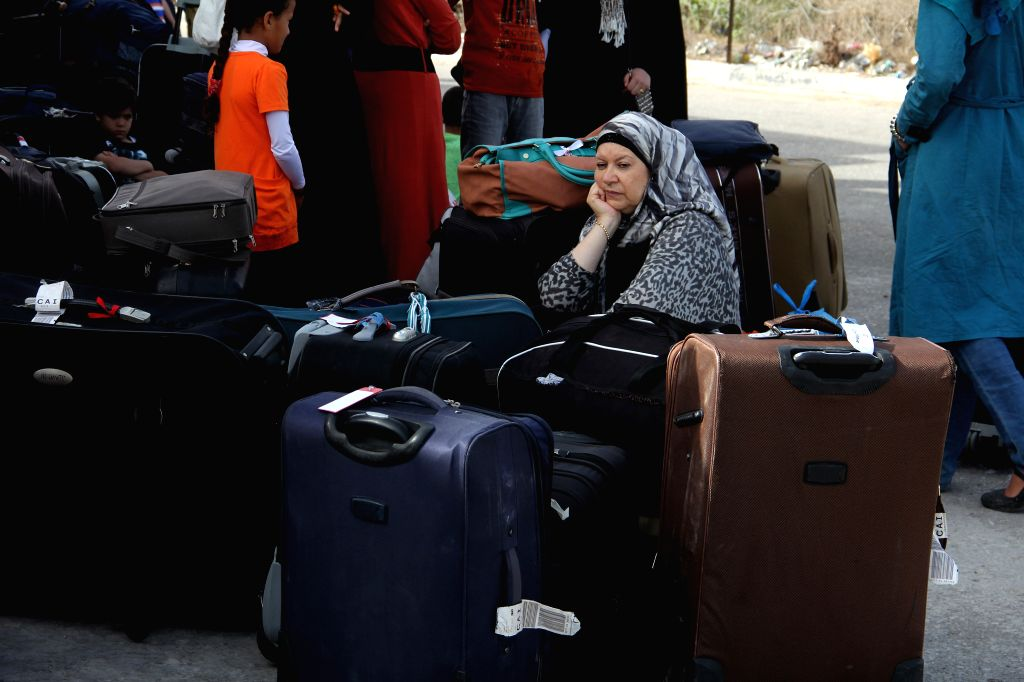 Gaza July 12, 2014  - A Palestinian woman hoping to cross into Egypt sits beside her luggage at the Rafah crossing between Egypt and the southern Gaza Strip on July 12, 2014. Egyptian ...