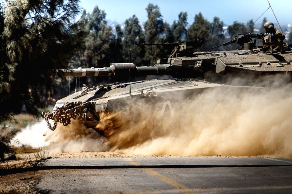 An Israeli Markava tank runs near the border between Israel and Gaza Strip on July 14, 2014. Israel's security cabinet decided on Tuesday morning to accept an Egyptian