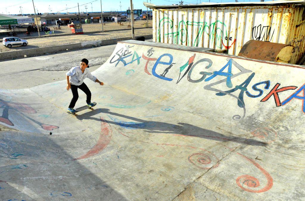 GAZA, July 16, 2019 - A Palestinian boy rides a skateboard near a port in Gaza City, July 15, 2019.