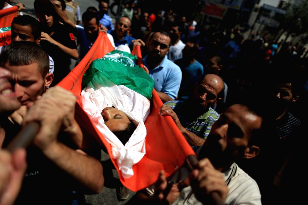 People carry the body of Walaa Abu Musallam, a Palestinian girl who was killed along with her two brothers in an Israeli tank attack, during their funeral in northern .
