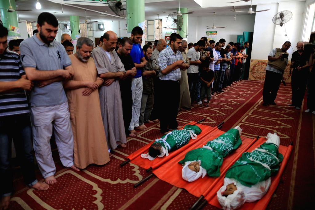 People pray over the bodies of three siblings of the Abu Musallam family, who were killed in an Israeli tank attack, during their funeral in northern Gaza strip town ..