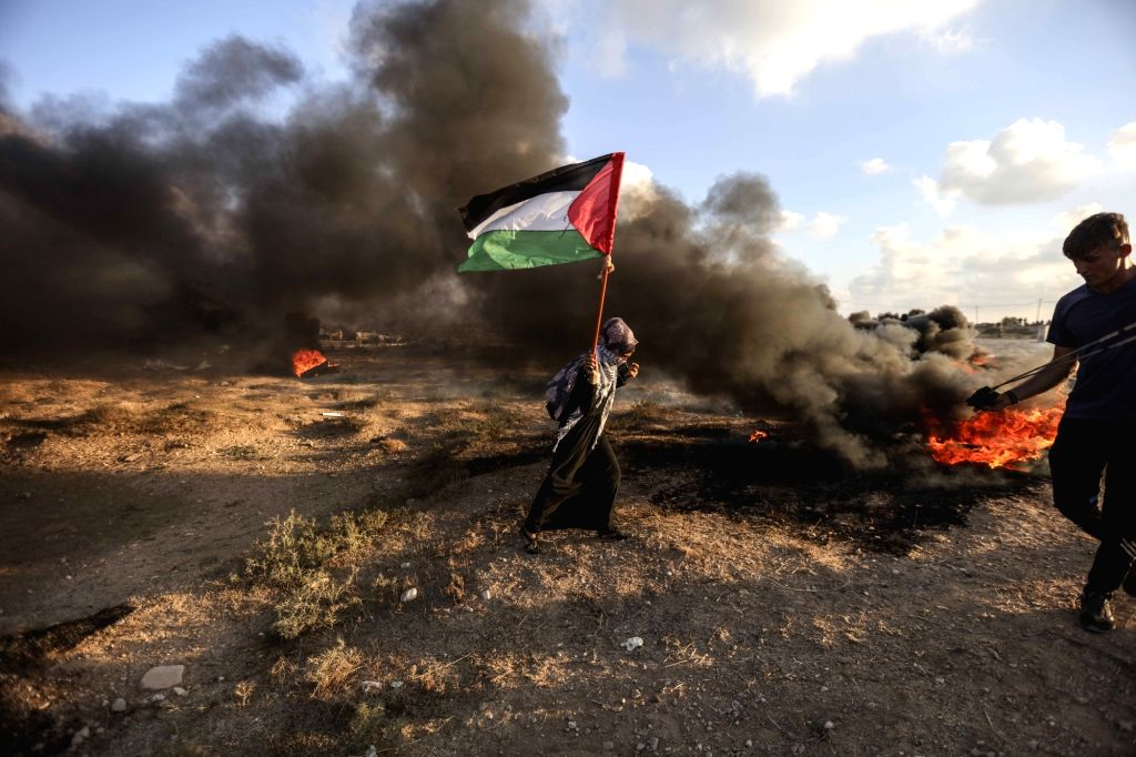 GAZA, July 20, 2018 - A Palestinian woman waves Palestinian flag during clashes with Israeli troops on the Gaza-Israel border, east of Gaza City, on July 20, 2018. Four Palestinians were killed and ...