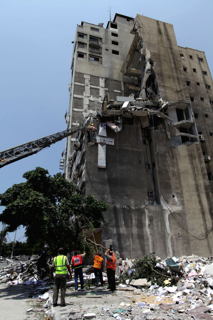 Palestinian members of civil defense inspect the rubble of a destroyed building following an Israeli airstrike in Gaza City on July 22, 2014. Ashraf al-Qedra, Gaza ...
