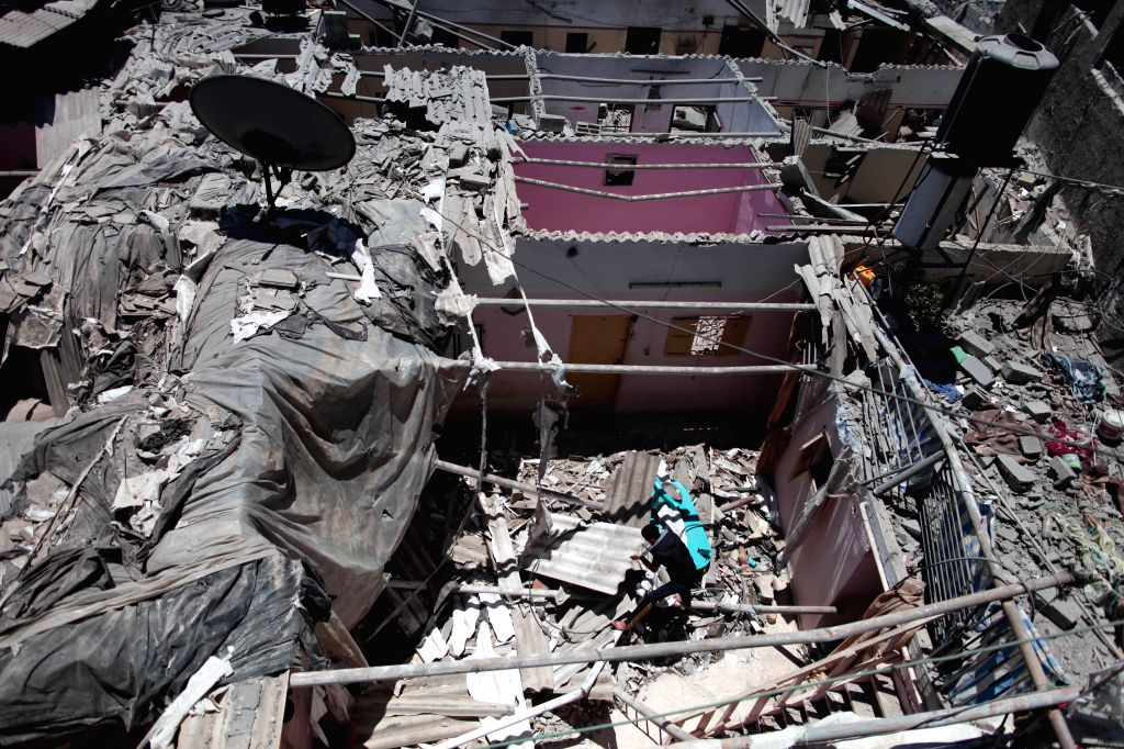 A Palestinian man is seen on the debris of a destroyed building following an overnight Israeli airstrike in Jabalia refugee camp, north of the Gaza Strip, on July 24, .
