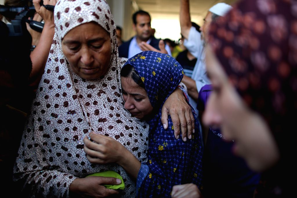 Palestinians mourn for their lost relatives at a hospital in Jabaliya, the northern Gaza Strip, on July 24, 2014. Four Israeli tank shells fired on Thursday at a ...