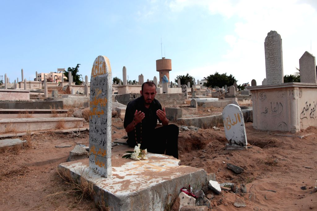 A Palestinian man prays over his relative's grave at the cemetery during the holiday of Eid al-Fitr in Gaza City on July 28, 2014.
