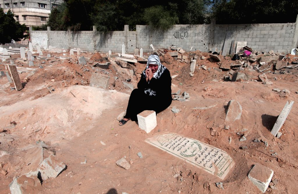A Palestinian woman prays over her relative's grave at the cemetery during the holiday of Eid al-Fitr in Gaza City on July 28, 2014.