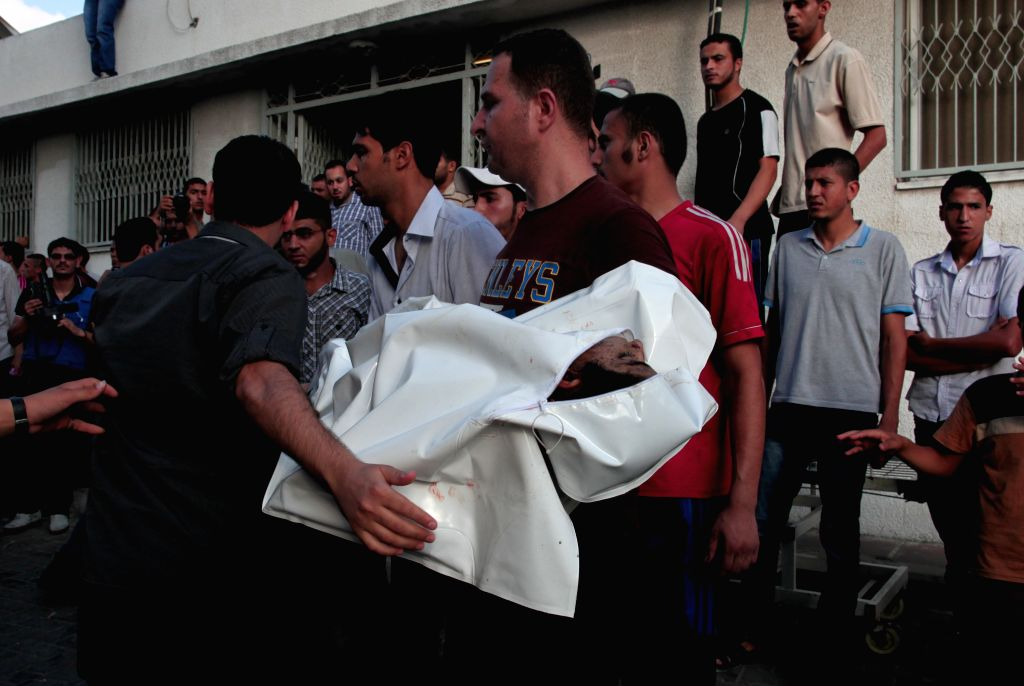 Palestinians carry the body of a child killed in an Israeli airstrike, outside the morgue of the al-Shifa hospital in Gaza City, July 28, 2014. Ten Palestinians were ..