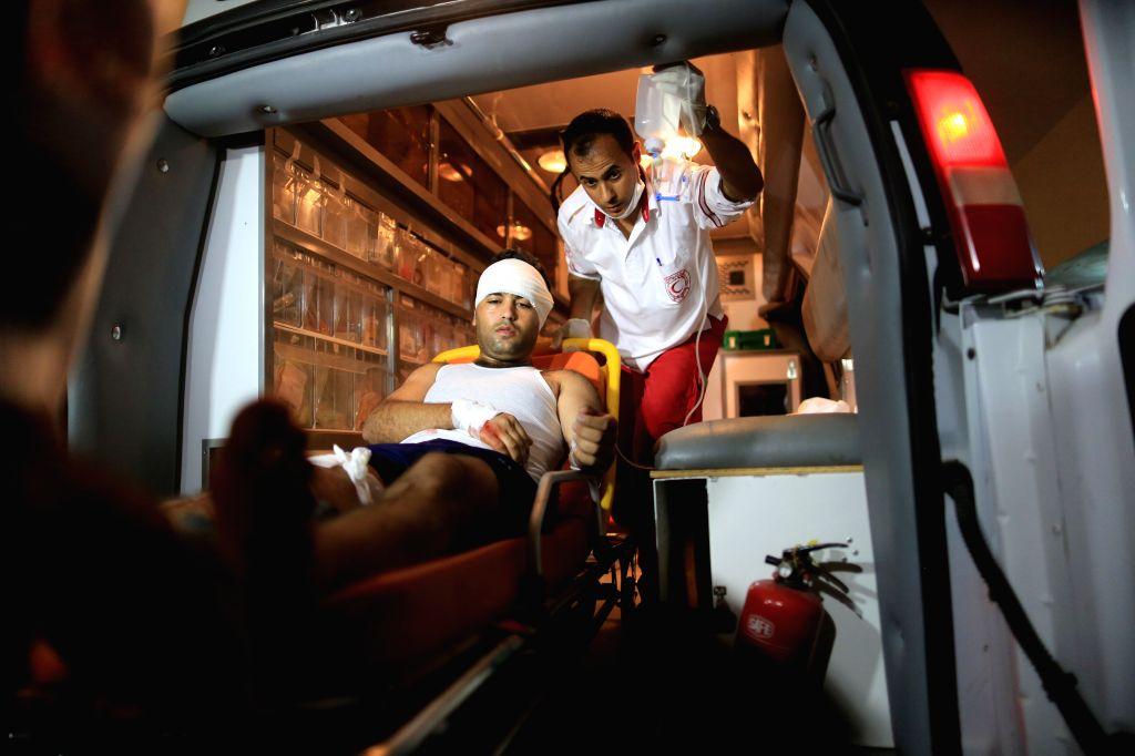 Medics treat a man, whom they said was wounded in an Israeli air strike, at a hospital in Gaza City on July 8, 2014. An Israeli senior military official said Tuesday ...