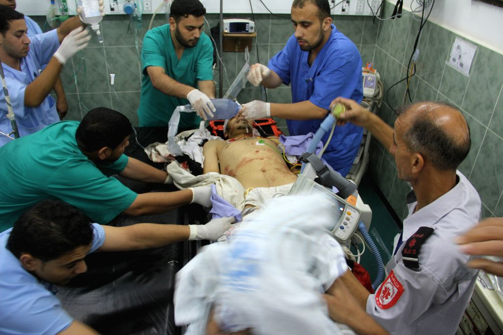 Doctors treat a Palestinian who they said was wounded in an Israeli airstrike, at a hospital in the southern Gaza Strip City of Rafah, on July 9, 2014. (Xinhua/Khaled ..