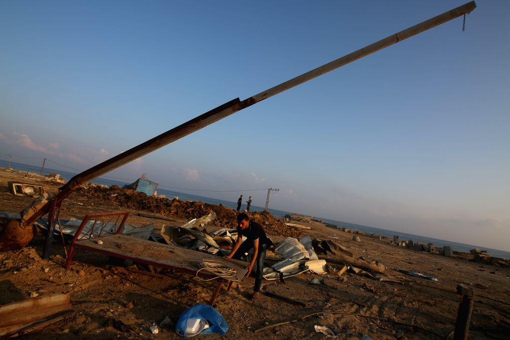 GAZA, June 14, 2019 - People check the site of an airstrike at a seaport under construction in the southern Gaza Strip city of Khan Younis, June 14, 2019. Israel struck on Friday militants' ...