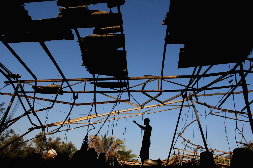 A palestinian inspects a damaged chicken coop after an Israeli airstrike in the southern Gaza Strip city of Khan Younis, on June 25, 2014.