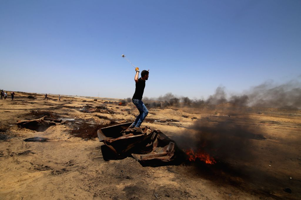 GAZA, June 8, 2018 - A Palestinian protester uses a slingshot to hurl stones at Israeli troops during clashes with Israeli troops, on the Gaza-Israel border, east of the southern Gaza Strip City of ...