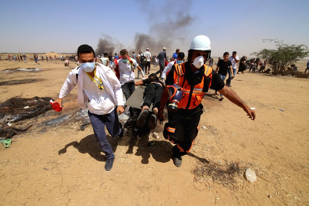 GAZA, June 8, 2018 - Palestinian medics carry a wounded man during clashes with Israeli troops, on the Gaza-Israel border, east of the southern Gaza Strip City of Khan Younis, on June 8, 2018. At ...